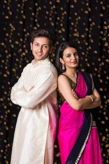 Ritratto di giovane coppia indiana allegra in abbigliamento tradizionale a diwali