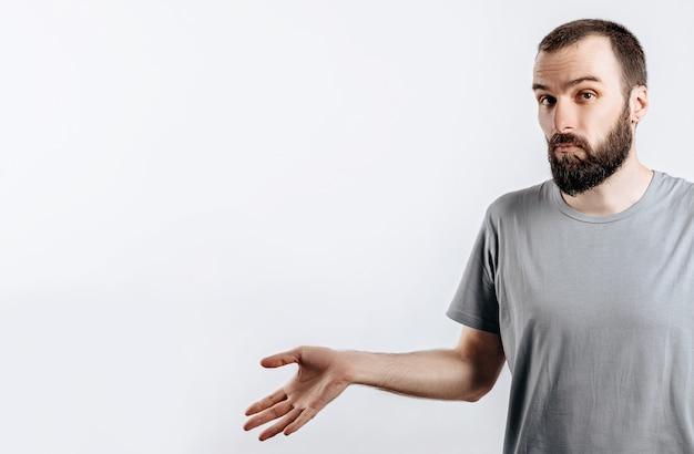 Ritratto di un giovane allegro che sorride mentre guarda la telecamera, alzando le mani ai lati dall'ignoranza su uno sfondo bianco con un posto per il mockup pubblicitario