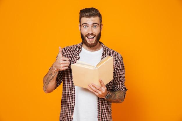 Ritratto di un giovane allegro che indossa abiti casual tenendo il libro di carta