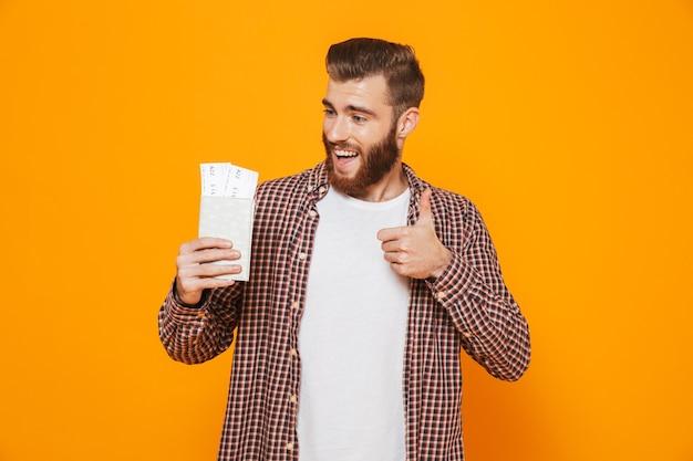 Ritratto di un giovane allegro che indossa abiti casual che mostra il passaporto con biglietti aerei