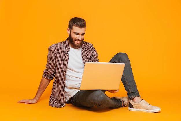 Ritratto di un giovane allegro che indossa abiti casual seduto tenendo il computer portatile