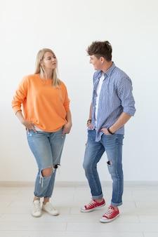 Ritratto di una giovane coppia positiva allegra in piena crescita vestita in abiti casual in posa su a