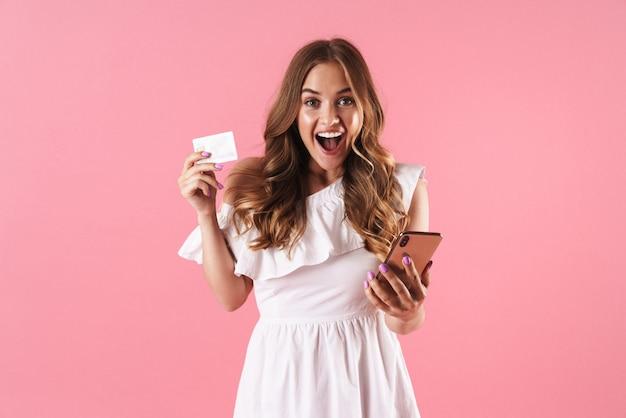 Ritratto di una giovane donna graziosa allegra che posa isolata sopra la parete rosa facendo uso della carta di credito della tenuta del telefono cellulare.