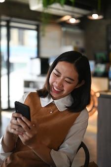 Ritratto di giovane donna allegra che naviga navigando in internet wireless su smartphone mentre è seduto al bar.