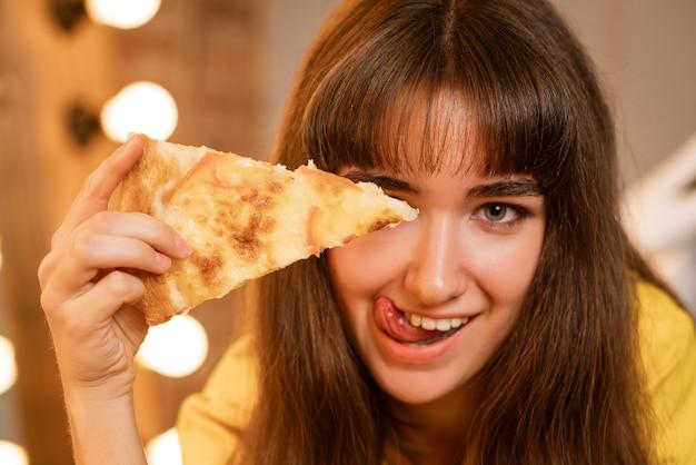 Ritratto di una giovane donna allegra in primo piano con una fetta di pizza