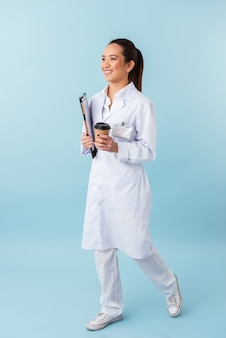Ritratto di un medico di giovane donna allegra in posa isolato sopra la parete blu che tiene appunti e bere caffè.