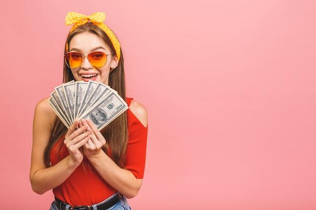 Ritratto di una giovane donna allegra che tiene le banconote dei soldi e che celebra isolate sopra fondo rosa