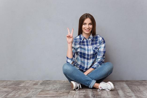 Ritratto di una giovane donna allegra seduta sul pavimento e che mostra il segno della vittoria sul muro grigio