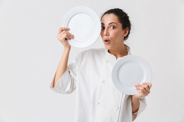 Ritratto di una giovane donna allegra che lava i piatti