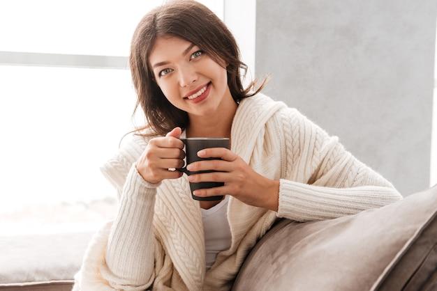 Ritratto di giovane donna allegra con l'ubicazione della tazza di caffè a casa