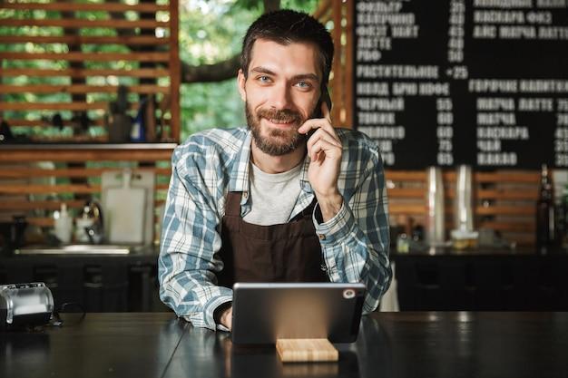 Ritratto di un allegro barista che indossa un grembiule utilizzando un computer tablet mentre si lavora in un caffè di strada o in un caffè all'aperto