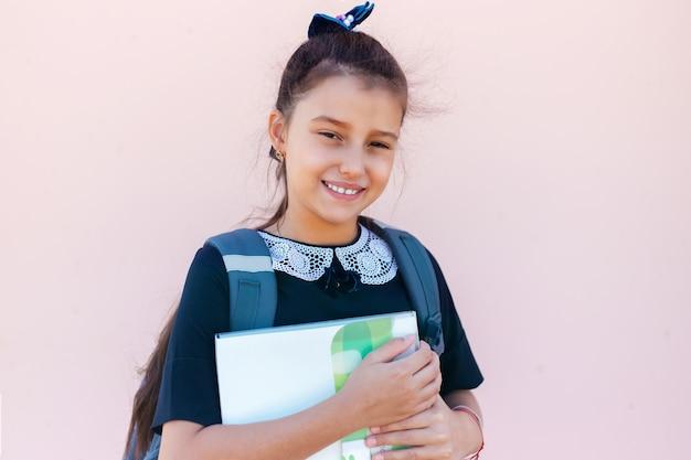 Ritratto di ragazza bambino con zaino in possesso di una cartella dopo la scuola su sfondo di colore rosa pastello.