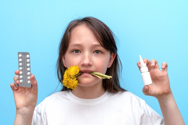 Ritratto di una bambina con fiori tra i denti e pillole antiallergiche e spray nelle sue mani