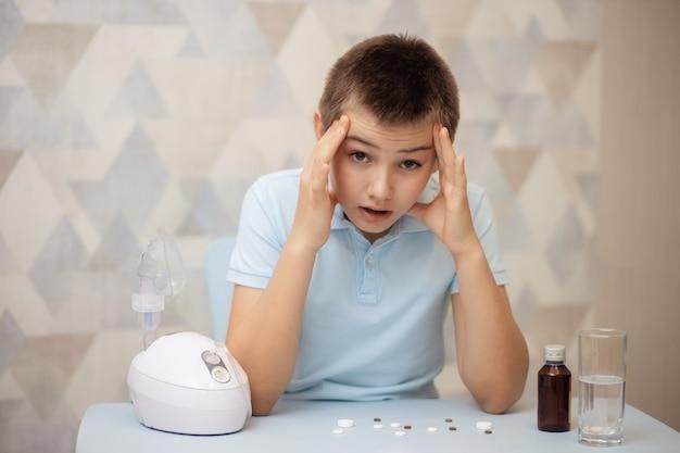 Ritratto di un bambino, un adolescente seduto a un tavolo con pillole e un inalatore, trattamento a casa