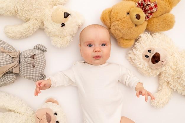 Ritratto di un bambino su un bianco con giocattoli di peluche.