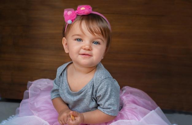 Ritratto di un bambino su uno sfondo di legno. bambino in abiti rosa.