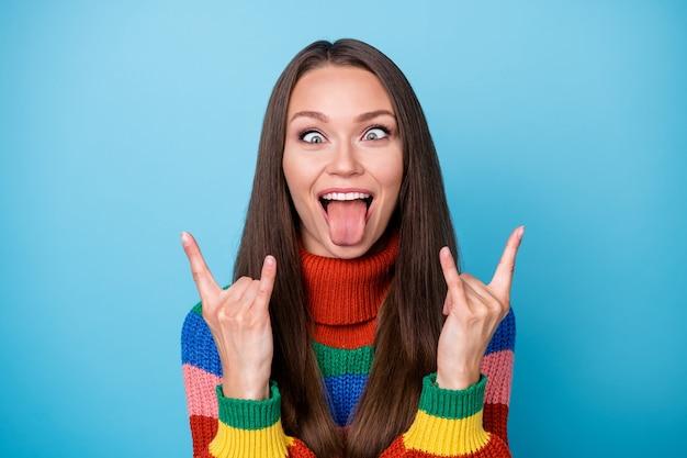 Ritratto di infantile giocoso pazzo gioventù ragazza studente ingannare fare simbolo cornuto mostra lingua fuori indossare stile elegante maglione alla moda isolato sopra priorità bassa di colore blu