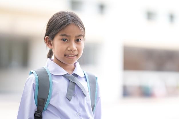 Ritratto di bambini studenti in uniforme e zaino guardando la telecamera che torna a scuola dopo la quarantena e il blocco del covid-19. torna al concetto di scuola stock photo