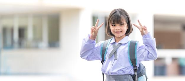 Ritratto di bambini studente in uniforme e zaino guardando la telecamera tornando a scuola