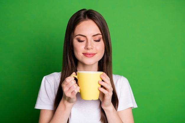 Ritratto di una ragazza bruna agghiacciante che beve odore di cacao indossa una maglietta bianca isolata su uno sfondo di colore verde