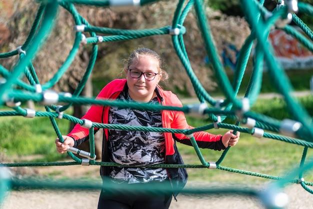 Ritratto di una ragazza bionda paffuta con gli occhiali in una corda piramidale parco giochi.