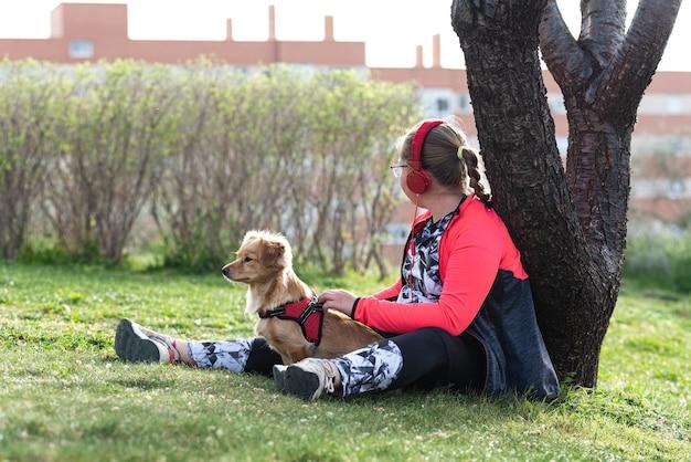 Ritratto di una ragazza bionda paffuta con gli occhiali che si siede sul prato con il suo cane. ascoltando la musica sul suo telefono cellulare con le cuffie.