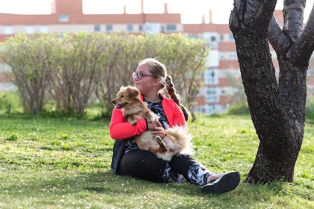 Ritratto di una ragazza bionda paffuta con gli occhiali che si siede sul prato con il suo cane.