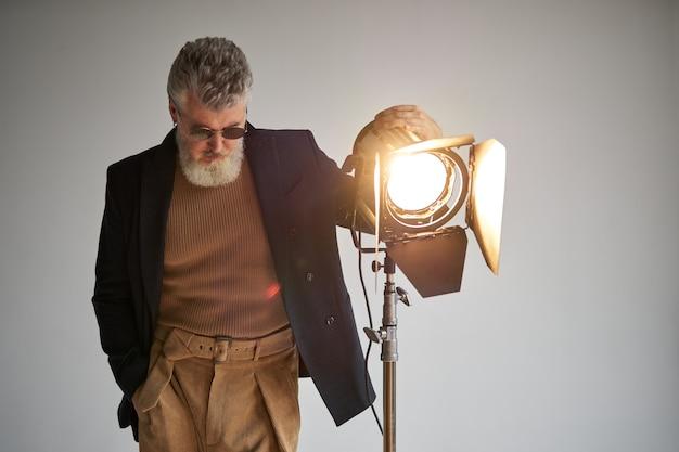 Ritratto di un uomo di mezza età barbuto di classe vestito elegantemente in piedi accanto al riflettore dello studio mentre