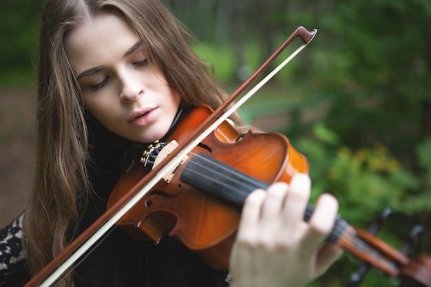 Ritratto ravvicinato di una bella ragazza violinista che ha abbassato gli occhi con entusiasmo suonando il violino romantico
