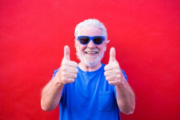 Ritratto e primo piano di un uomo maturo che fa il segno di sì con le dita in alto - anziano con occhiali da sole blu e maglietta sorridente e guardando la telecamera divertendosi - sfondo rosso