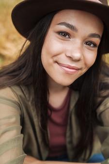 Primo piano del ritratto di una donna adorabile con lunghi capelli scuri che indossa un cappello che sorride alla telecamera mentre si fa selfie