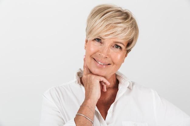 Primo piano del ritratto di bella donna adulta con capelli biondi corti che sorride alla macchina fotografica isolata sopra la parete bianca in studio