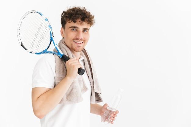 Primo piano del ritratto dell'uomo caucasico con l'asciugamano che tiene la racchetta e la bottiglia d'acqua mentre gioca a tennis isolato sopra la parete bianca