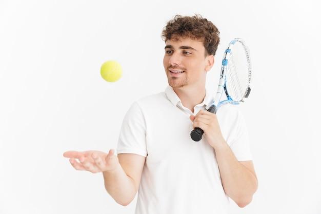 Primo piano del ritratto dell'uomo allegro in maglietta che tiene racchetta e palla mentre gioca a tennis isolato sopra la parete bianca