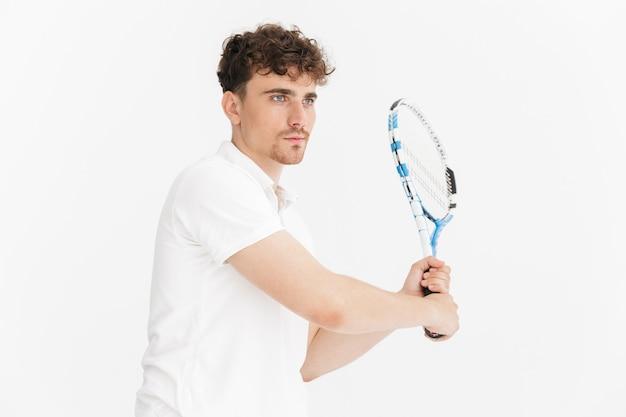 Primo piano del ritratto dell'uomo sicuro in maglietta che guarda da parte e tiene la racchetta mentre gioca a tennis isolato sopra la parete bianca