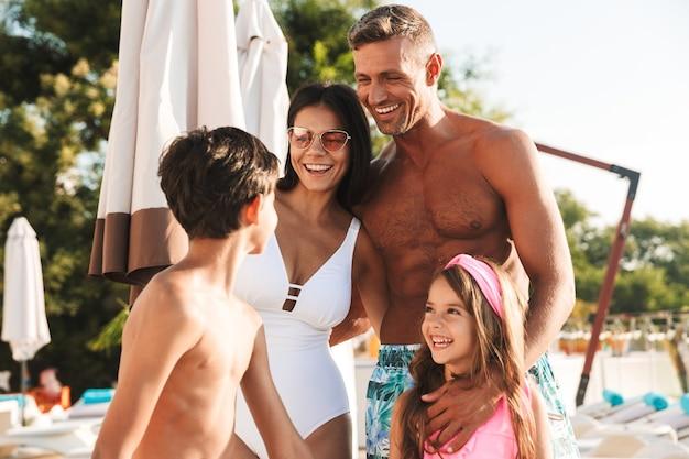 Primo piano del ritratto di gioioso uomo europeo e donna con bambini sorridenti, mentre riposa vicino alla lussuosa piscina con sdraio e ombrelloni durante le vacanze