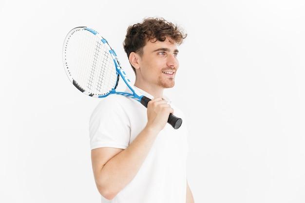 Primo piano del ritratto dell'uomo gioioso in maglietta che guarda da parte e tiene la racchetta mentre gioca a tennis isolato sopra la parete bianca