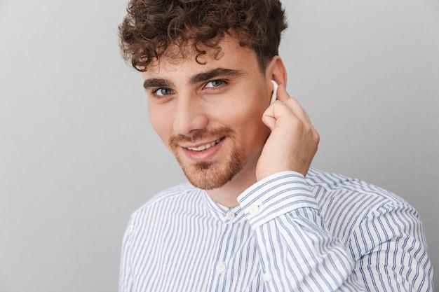 Primo piano del ritratto del giovane maschile con i padiglioni auricolari che sorride alla macchina fotografica isolata sopra il muro grigio