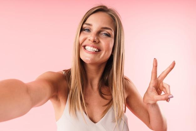 Primo piano del ritratto di giovane donna seducente che mostra le dita di pace e sorride alla macchina fotografica mentre prende selfie ritratto isolato sopra la parete rosa
