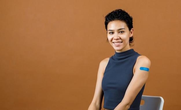 Ritratto closeup studio mug shot di carina bella paziente femminile sexy sorridente che mostra una benda di gesso blu sulla spalla dopo aver ricevuto la vaccinazione contro il coronavirus covid-19 davanti al muro marrone.