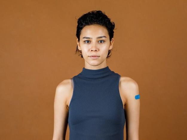 Ritratto closeup studio mug shot di una bella paziente sexy carina che sorride mostrando una benda di gesso blu sulla spalla dopo aver ricevuto la vaccinazione contro il coronavirus covid-19 davanti al muro marrone.