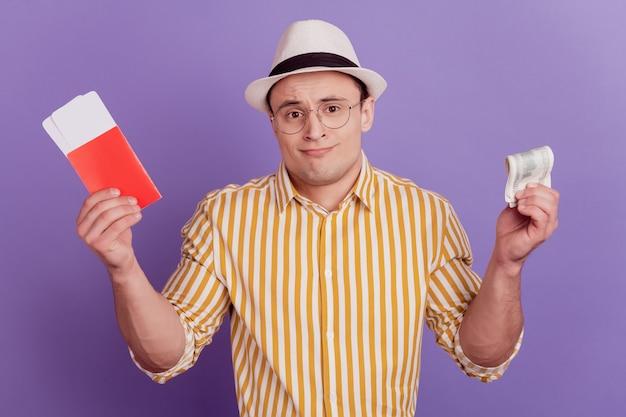 Ritratto di un ragazzo incerto e incerto che tiene i biglietti della banconota del dollaro con un'alzata di spalle su sfondo viola