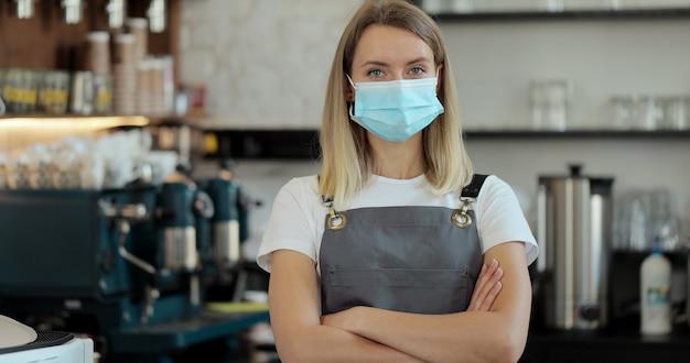 Ritratto della donna del ristorante della caffetteria in maschera di protezione medica del viso, impiegato, la quarantena del coronavirus è finita. piccola impresa dopo il covid.