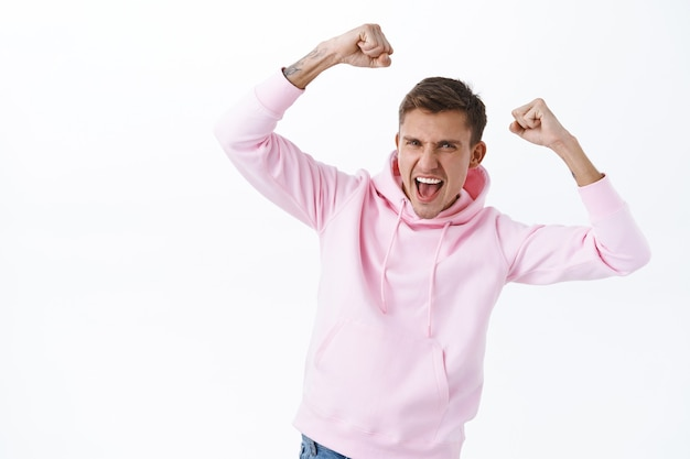 Ritratto di un ragazzo biondo felice e di successo competitivo che alza le mani e balla come un campione, gridando sì, vincendo la competizione, raggiunge l'obiettivo, diventa vincitore, trionfa sul muro bianco