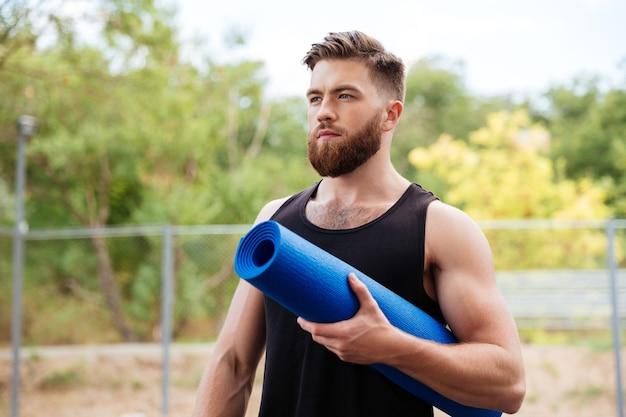 Ritratto di un uomo sportivo barbuto concentrato che tiene un tappetino da yoga all'aperto