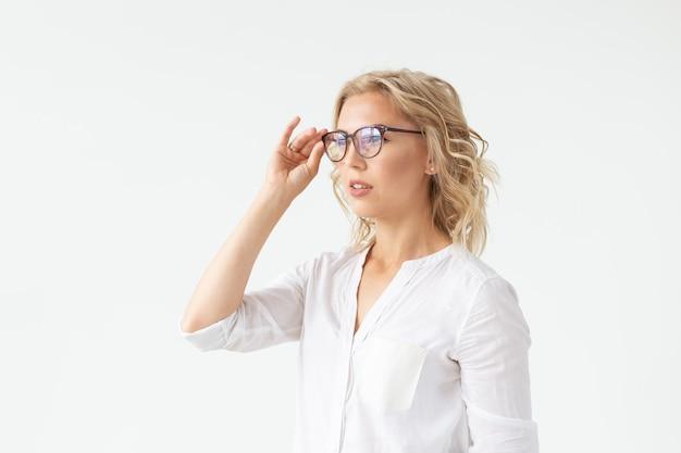 Ritratto di bella donna concentrata con vista difettosa che tocca i vetri isolati sulla parete bianca.