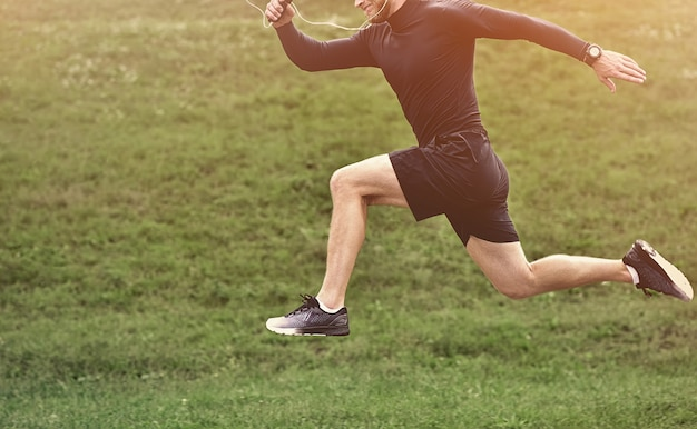 Ritratto di concentrato fiducioso muscolare pieno di forza sportivo che indossa pantaloncini e scarpe da ginnastica.