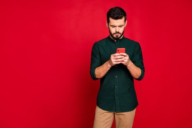 Ritratto di ragazzo concentrato utilizza il suo smartphone per risolvere problemi di lavoro sui social network indossare pantaloni pantaloni stile casual marrone