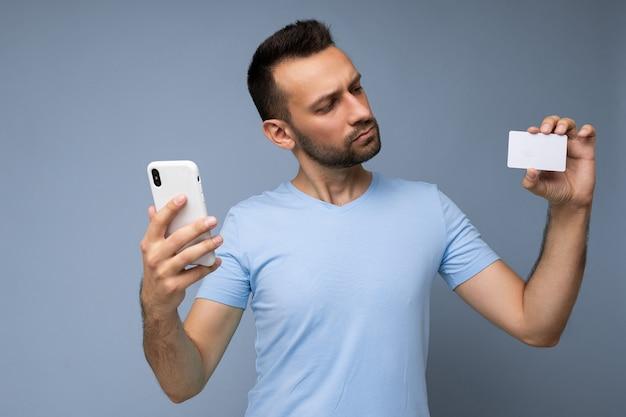 Ritratto di un bell'uomo concentrato che indossa abiti di tutti i giorni isolato su una parete di fondo che tiene e utilizza il telefono e la carta di credito che effettuano pagamenti guardando la carta bancaria di plastica