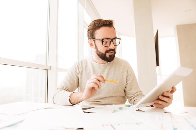 Ritratto di un uomo concentrato che lavora con i documenti